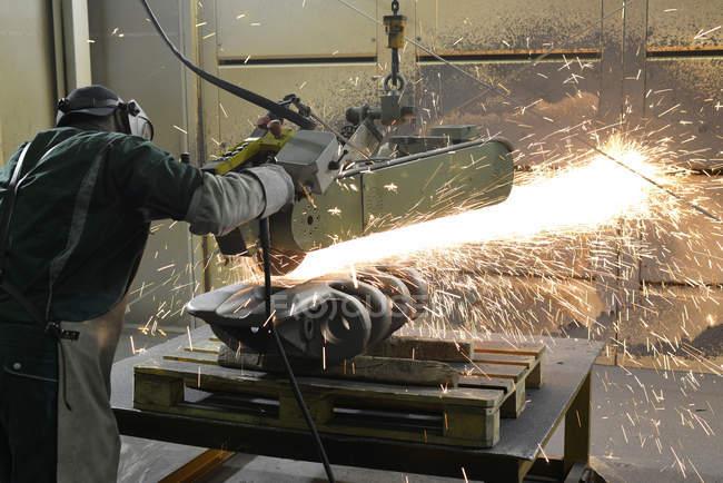 Человек работает с ленточным шлифовальным станком в литейном цехе — стоковое фото