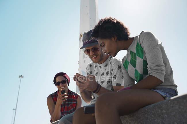 Amigos usando telefones celulares ao ar livre — Fotografia de Stock