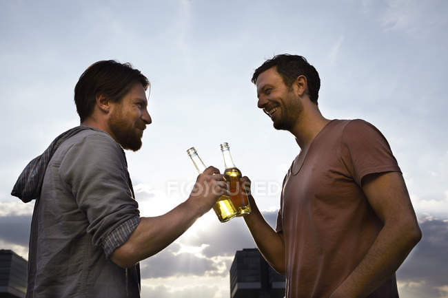 Two friends with beer bottles outdoors — Stock Photo