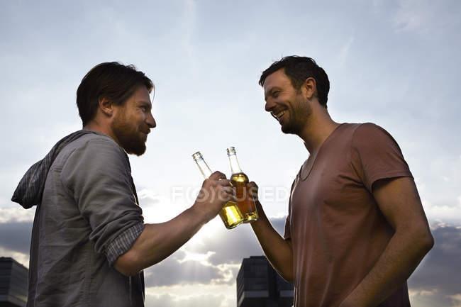 Dois amigos com garrafas de cerveja ao ar livre — Fotografia de Stock