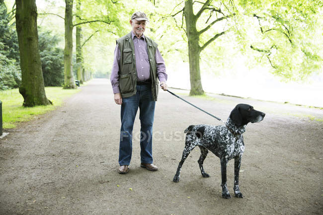 Senior man walking with dog in park — Stock Photo