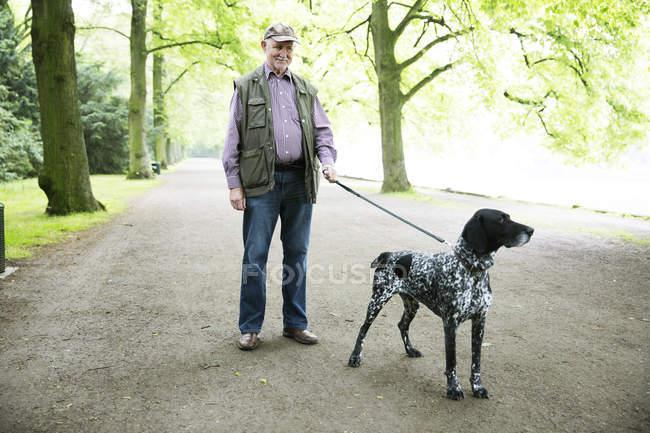 Uomo anziano che cammina con cane nel parco — Foto stock