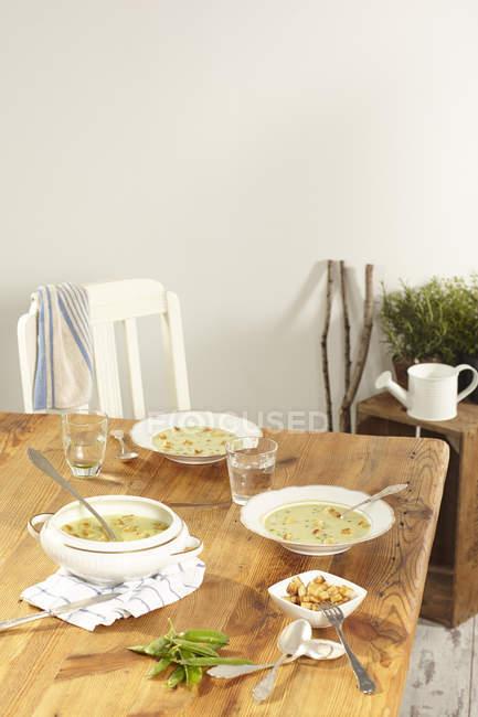 Hausgemachte Erbsensuppe mit Croutons auf Küchentisch — Stockfoto