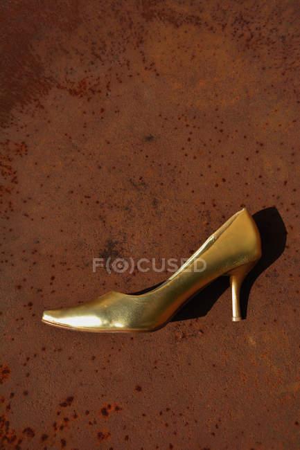 Estilete dorado sobre una mesa oxidada de madera - foto de stock