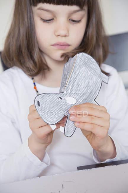 Little girl tinkering paper hippo — Stock Photo