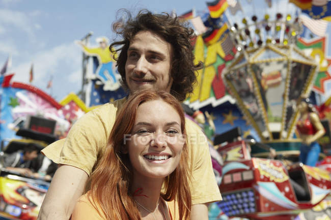 Happy young couple on a funfair, colorful attractions on background — Stock Photo