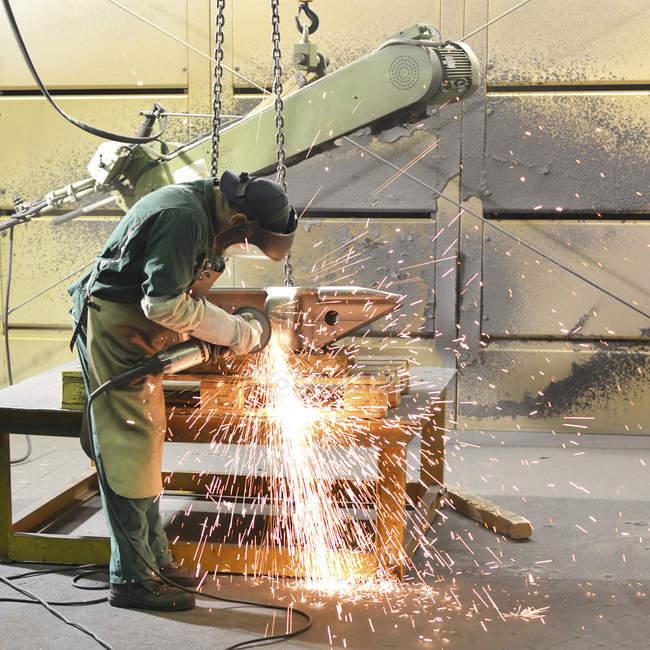 Travailleur à l'aide de la machine de meulage — Photo de stock