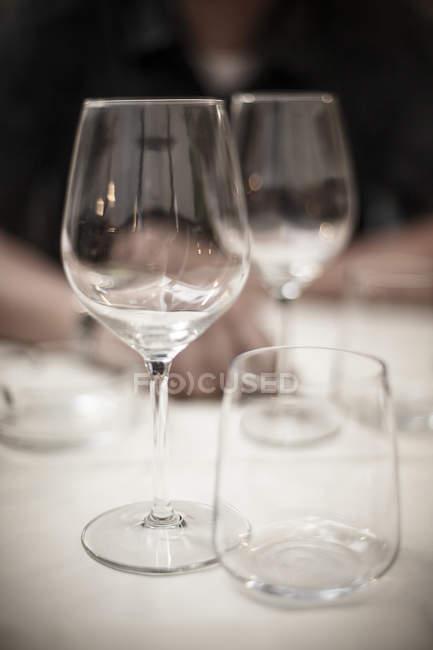 Three empty glasses on white table — Stock Photo