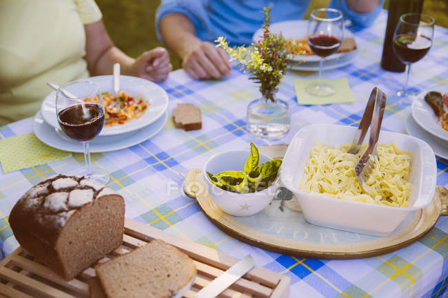 Table with pasta, bread and wine in evening light — Stock Photo
