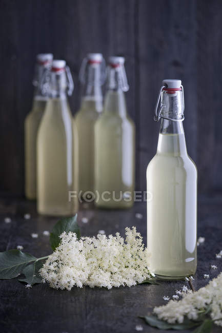 Glass bottles of home-made elderflower sirup and elderflowers on dark wood — Stock Photo