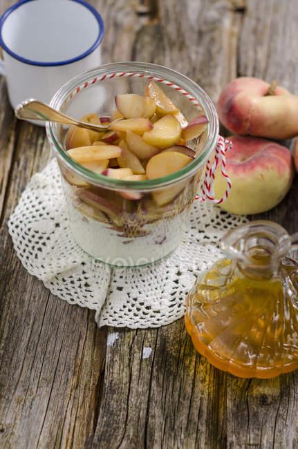 Vidro de pêssegos no iogurte natural e garrafa de xarope de pêssego — Fotografia de Stock