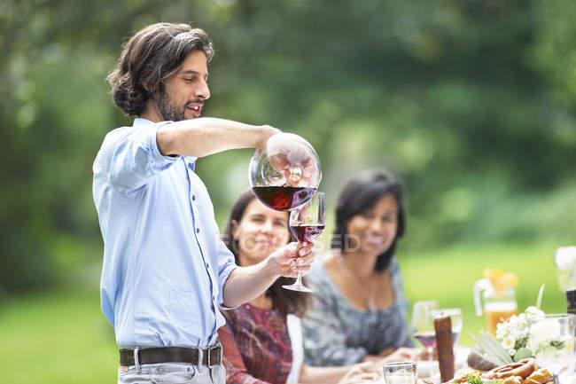 Man gießt Rotwein auf einer Gartenparty — Stockfoto