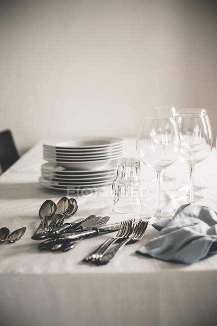 Table with stack of plates, wine and water glasses and silver cutlery — Stock Photo