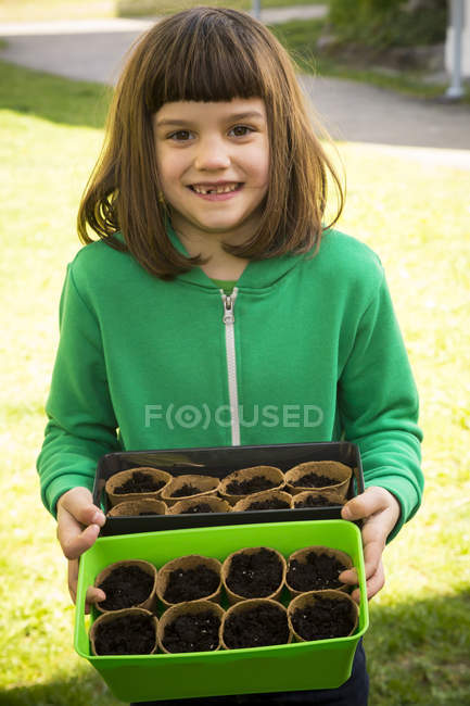 Girl holding boxes with nursery pots — Stock Photo