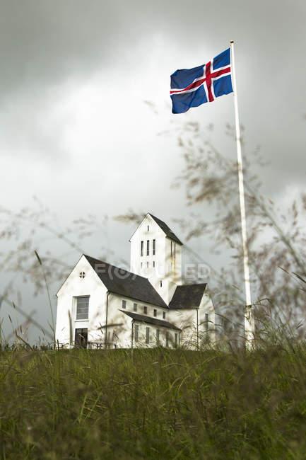 Mostra alla Chiesa di Skálholt con il salto bandiera nazionale sul flaspole in primo piano, Islanda — Foto stock