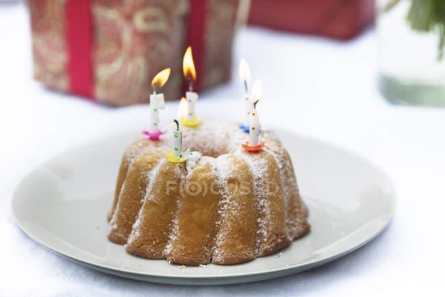 Torta di compleanno con le candele di illuminazione u al forno