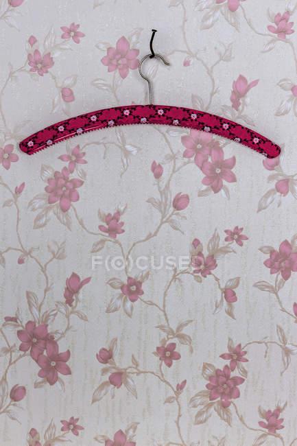 Cabide de roupas fixo com um prego curvado pendurado no papel de parede com design floral rosa — Fotografia de Stock