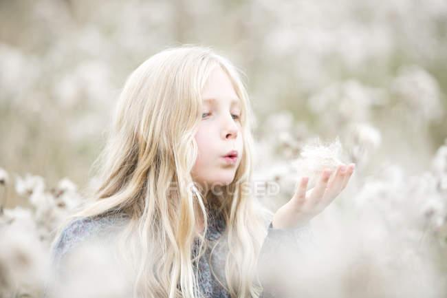 Retrato de menina em pé em um campo que soprar as sementes fora de sua mão — Fotografia de Stock
