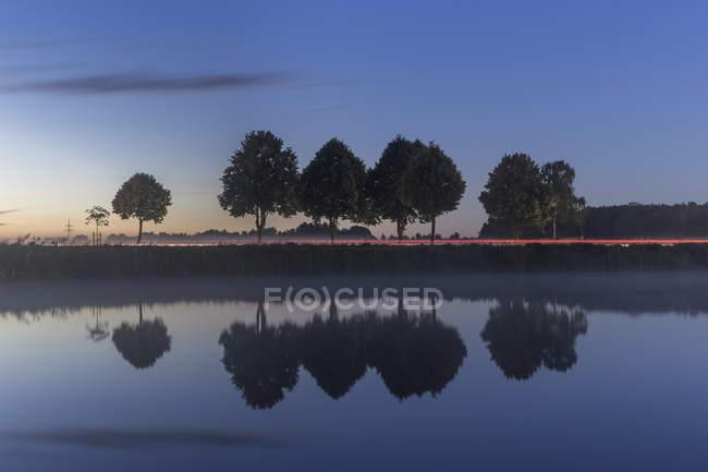 Alemania, Baja Sajonia, Gifhorn, Lago y reflejos de árboles, Camino con sendero ligero por la noche - foto de stock