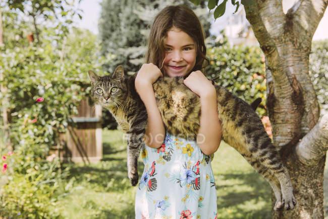 Молодая кавказская девушка держит кошку в саду — стоковое фото