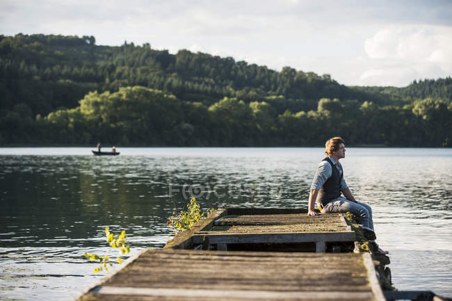 Germany, Rhineland-Palatinate, Laach Lake, Man sitting on wooden boardwalk — Stock Photo