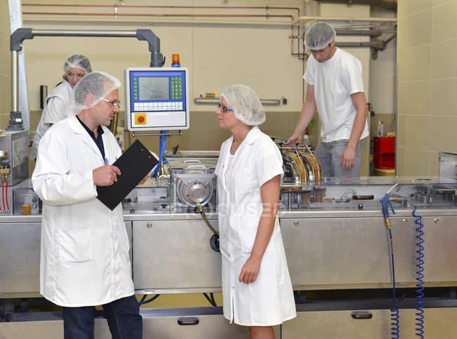 Personnel parlant près de machines dans une usine de boulangerie — Photo de stock