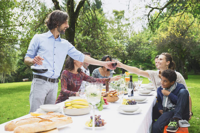 People pouring red wine on garden party — Stock Photo