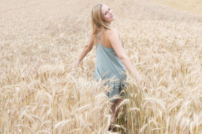 Porträt der lächelnde junge Frau mit ausgestreckten Armen in einem Roggenfeld stehen — Stockfoto