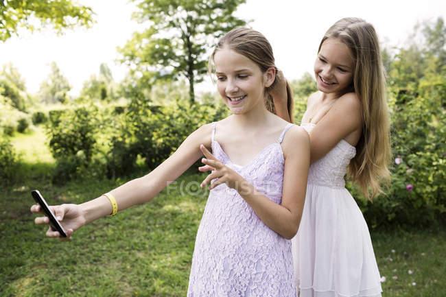 Девушка делает селфи, пока ее сестра расчесывает волосы — стоковое фото