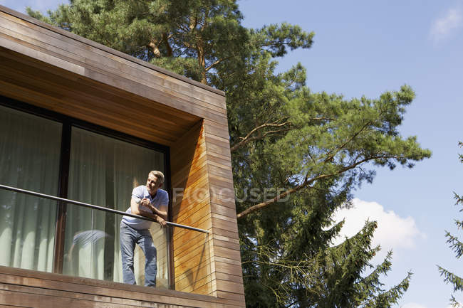 Mature man standing on balcony and relaxing — Stock Photo