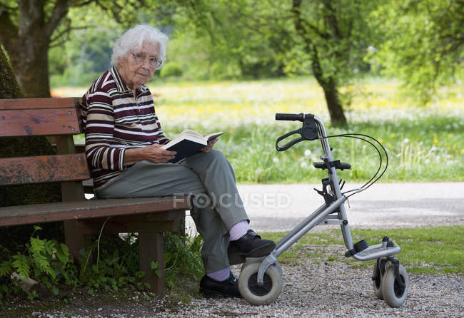 Senior woman sitting on bench and reading book — Stock Photo
