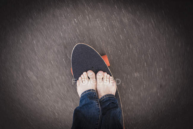 Mature man standing on skateboard — Stock Photo