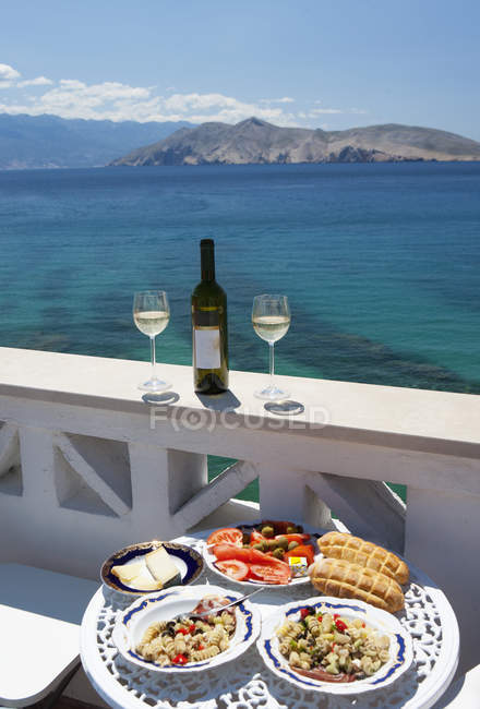 Croatia, Table laid with food in restaurant, adriatic sea in background at Baska — Stock Photo