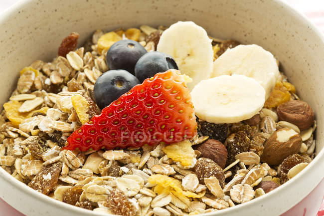 Breakfast bowl of cereals with banana, blueberries and strawberries — Stock Photo