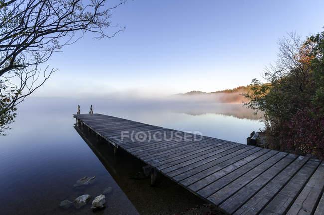 Germania, Baviera, Veduta del lago Kirchsee con pontile nella nebbia — Foto stock