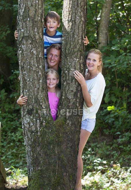 Ritratto degli amici in piedi dietro il tronco d'albero, sorridente — Foto stock