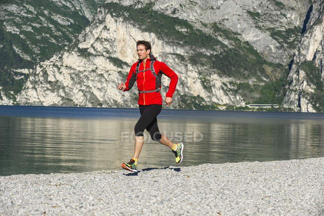 Италия, взрослый мужчина бегает трусцой по озеру Гарда — стоковое фото