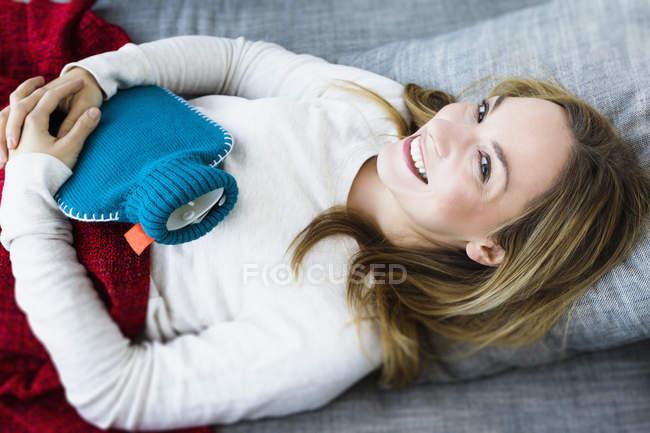 Портрет молодой женщины, лежащей на диване с бутылкой горячей воды, улыбающейся — стоковое фото
