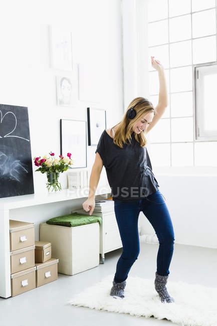 Молодая женщина слушает музыку и танцует — стоковое фото