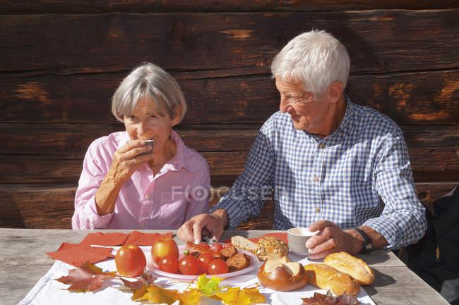 Пожилые супружеские пары, едят альпийских перекусить в горной хижине — стоковое фото