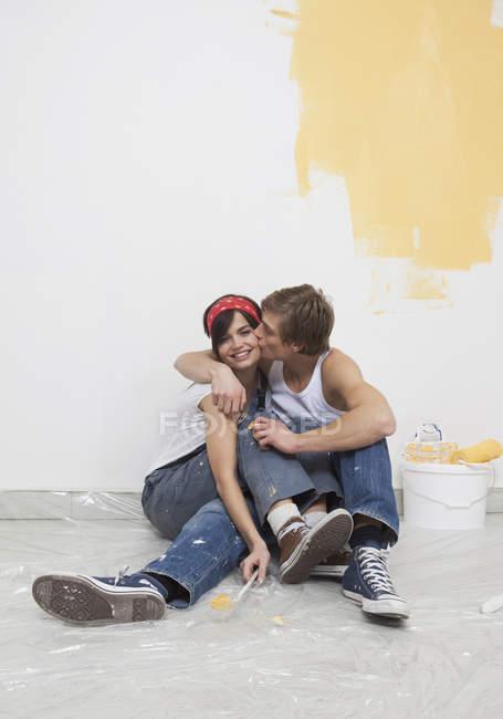 Молодая пара рисует новый дом и улыбается — стоковое фото