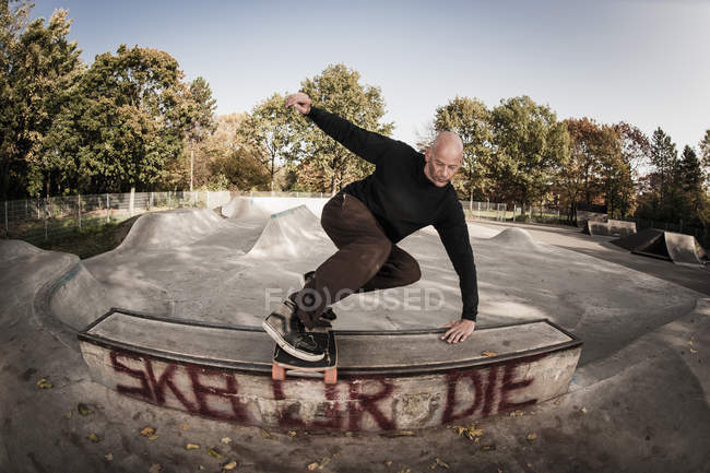 Mature man jumping with skateboard — Stock Photo
