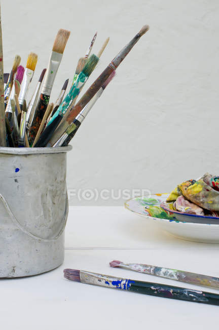 Paint brushes, palette and cloth on table — Stock Photo