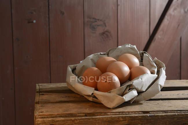 Œufs bruns biologiques en papier sur caisse en bois — Photo de stock