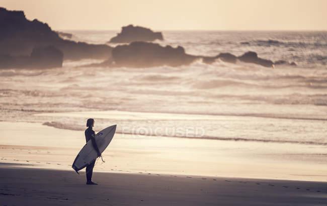 Portugal, Algarve, Sagres, seascape do sol cênico com silhueta de surfista com prancha de surf na Praia Castelejo, olhando para o oceano — Fotografia de Stock