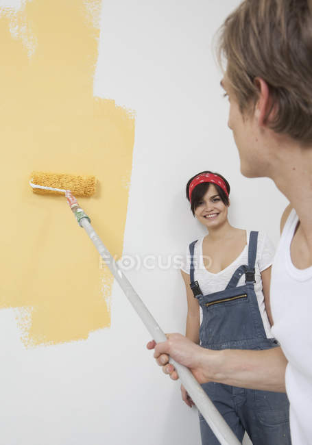Young couple painting new home and smiling — Stock Photo