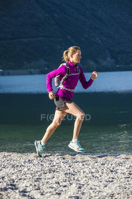 Italie, Femme adulte moyenne jogging au bord du lac de Garde — Photo de stock