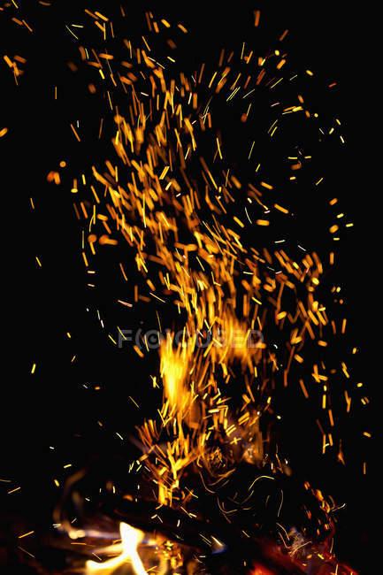 Ansicht von Funken aus Lagerfeuer auf schwarzem Hintergrund — Stockfoto