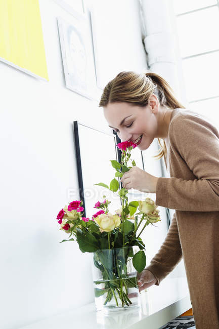 Young woman smelling flowers, smiling — Stock Photo