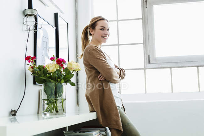 Portrait of young woman leaning on shelf, smiling — Stock Photo